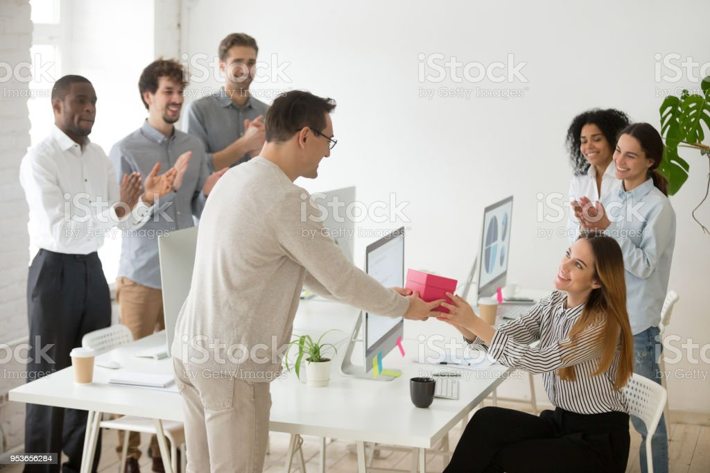 Friendly Team Congratulating Female Colleague With Birthday Gift And Applauding Royalty Free Stock Photo