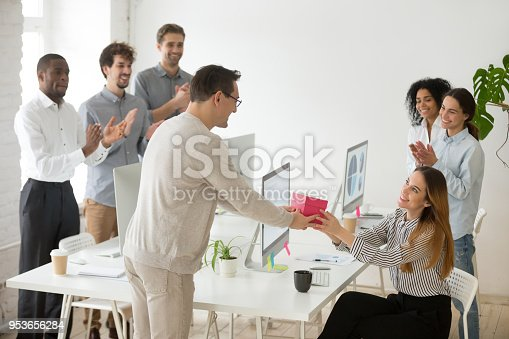 istock Friendly team congratulating female colleague with birthday gift and applauding 953656284