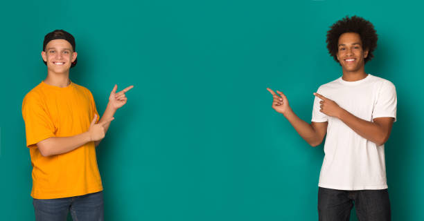 Friendly teen boys pointing on copy space Friendly teen boys pointing on copy space over blue background male likeness stock pictures, royalty-free photos & images