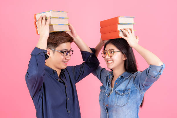 Friendly teenage man and woman place stack books on head stock photo
