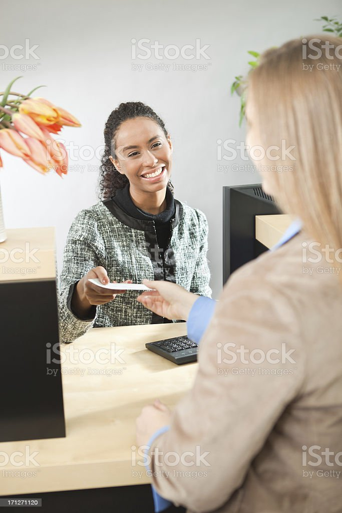 A Caucasian woman bank customer making a transaction with a bank...