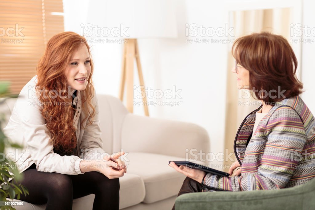 Friendly therapist supporting red-haired woman stock photo