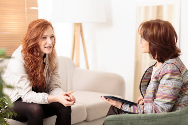 friendly therapist supporting red-haired woman - psychiatrist stock photos and pictures