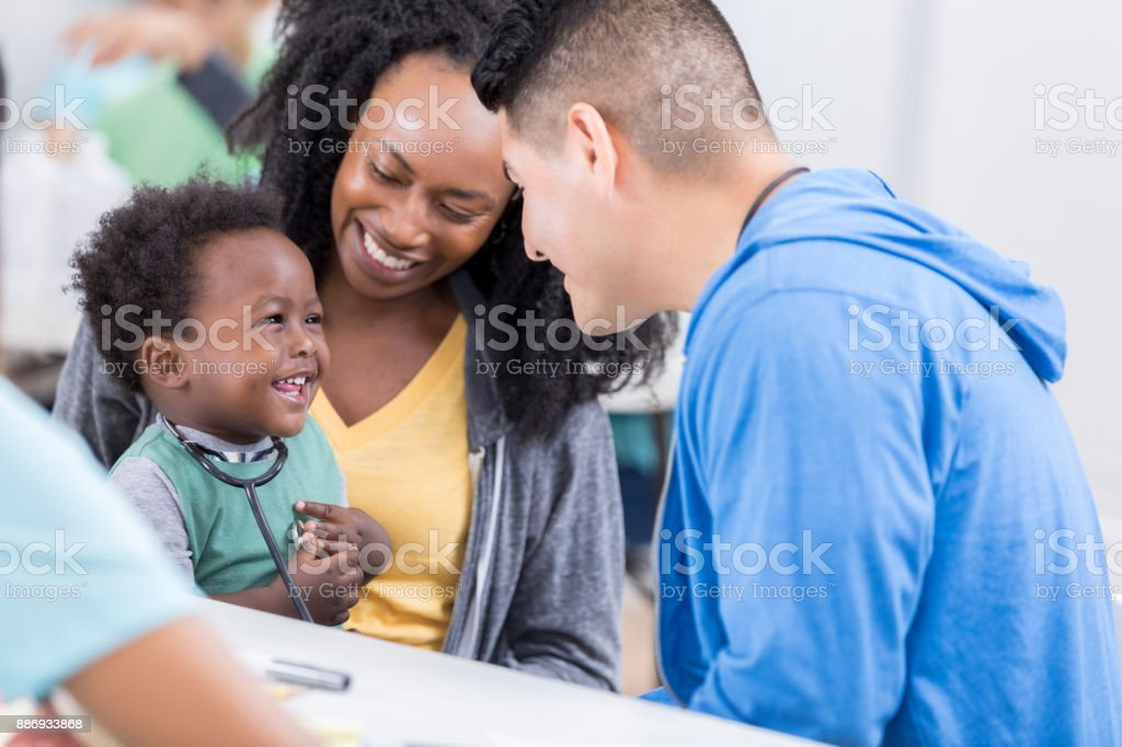 Friendly volunteer pediatrician talks to baby boy stock photo