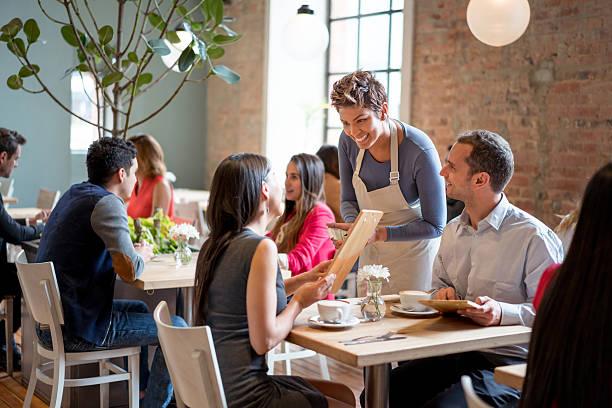 freundliche kellnerin serviert paar in einem restaurant - bestellen stock-fotos und bilder