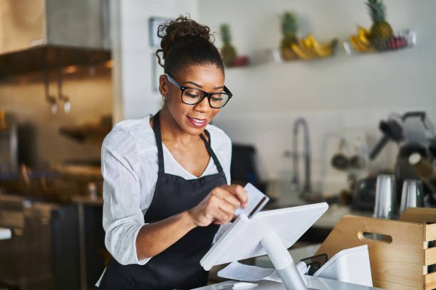 friendly waitress swiping bank card on pos terminal in restaurant stock photo