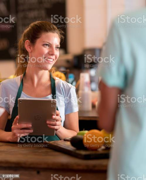 Friendly waitress taking an order with a computer tablet behind the picture id919359186?b=1&k=6&m=919359186&s=612x612&h=hekmfych6p0yoswhzdiwift5igsps icj6vx053 1im=