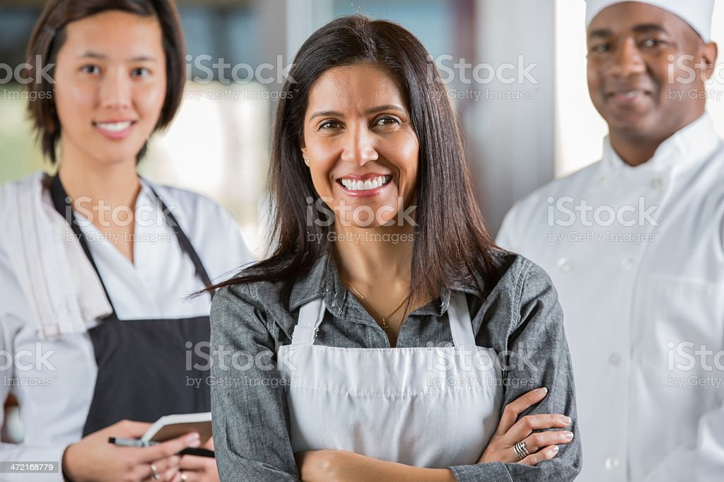 Friendly waitstaff and chef in modern restaurant royalty-free stock photo