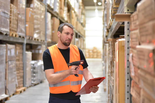 friendly warehouse worker in a warehouse with the barcode scanner stock photo
