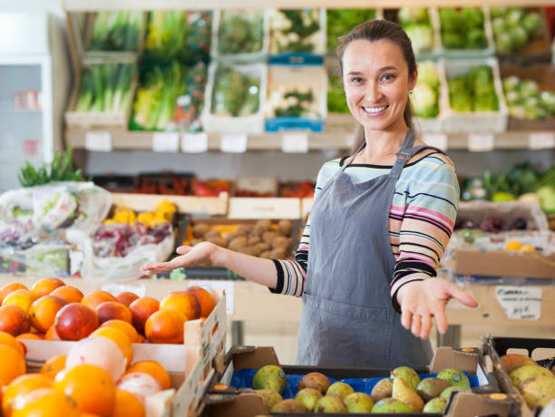 friendly woman seller  at fruit department stock photo