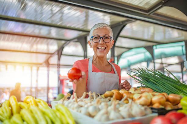 donna amichevole che si occupa di un ortaggio biologico - bazar mercato foto e immagini stock