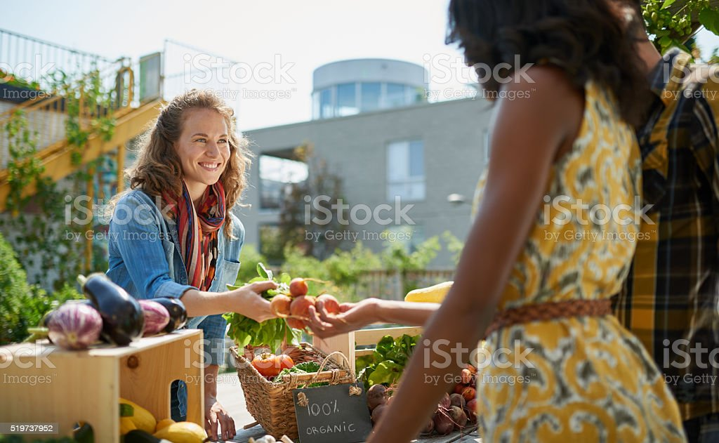 Friendly woman tending an organic vegetable stall at a farmer Female gardener selling organic crops and picking up a bountiful basket full of fresh produce Active Lifestyle Stock Photo