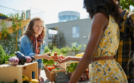 Friendly Woman Tending An Organic Vegetable Stall At A Farmer Stock Photo - Download Image Now