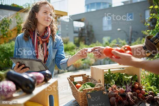 Friendly woman tending an organic vegetable stall at a farmer picture id526709144?b=1&k=6&m=526709144&s=612x612&h=qw9durtijvyj54e 1aixyb4rim0tlgyvqis tfdcvlc=