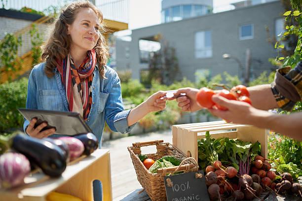 donna prendendoci cura di organico e verdura chiosco presso un agricoltore - mercato luogo per il commercio foto e immagini stock
