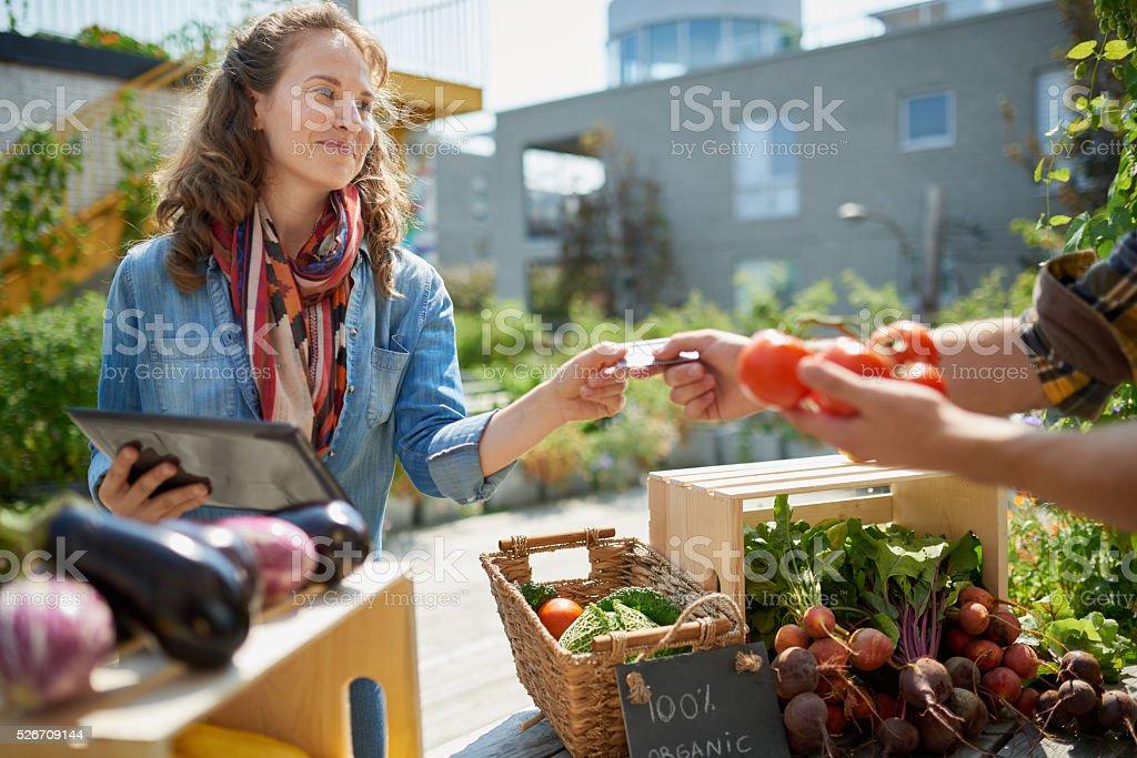 Amable mujer tiende un máximo de vegetales orgánicos de la granja - foto de stock
