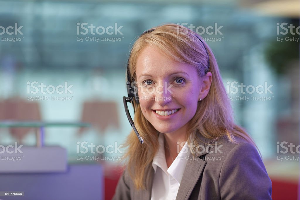 friendly woman with headset at helpdesk stock photo