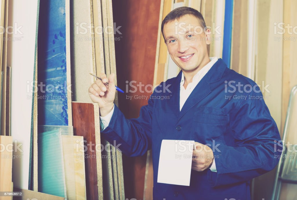 friendly workman standing with plywood pieces stock photo