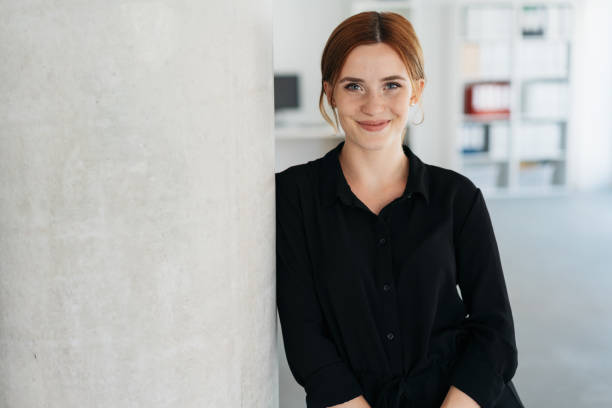 Friendly young businesswoman smiling at camera stock photo