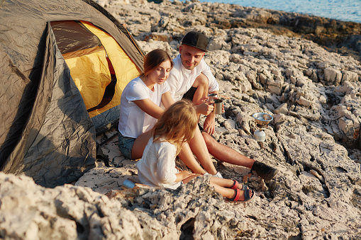 Friendly young family, sitting on ground near tent on stone seacoast
