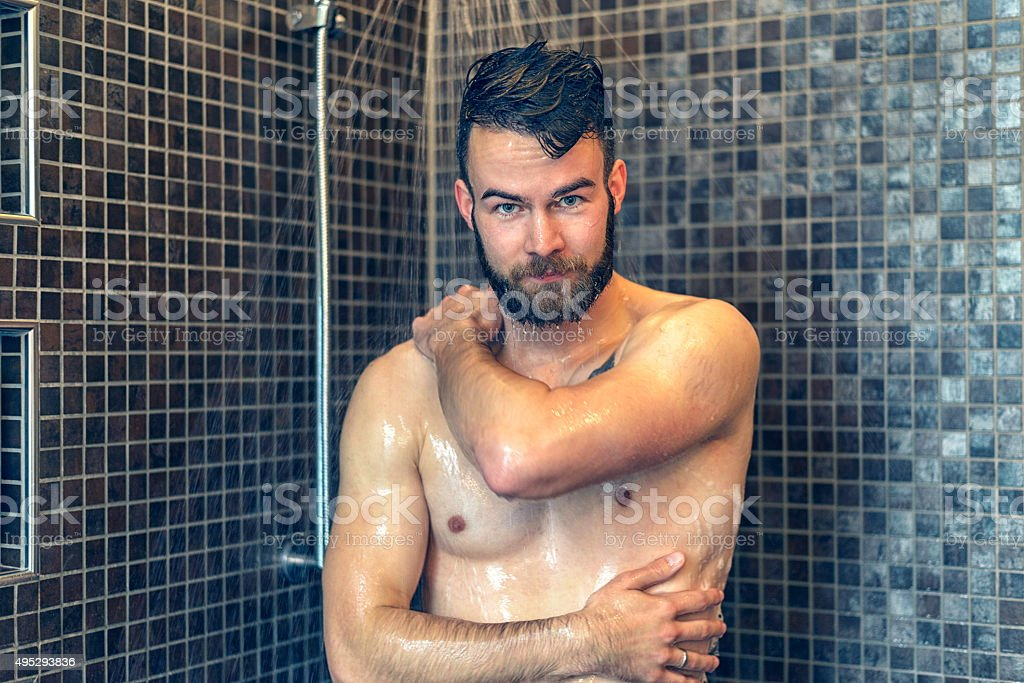 Friendly young man soaping himself in the shower stock photo