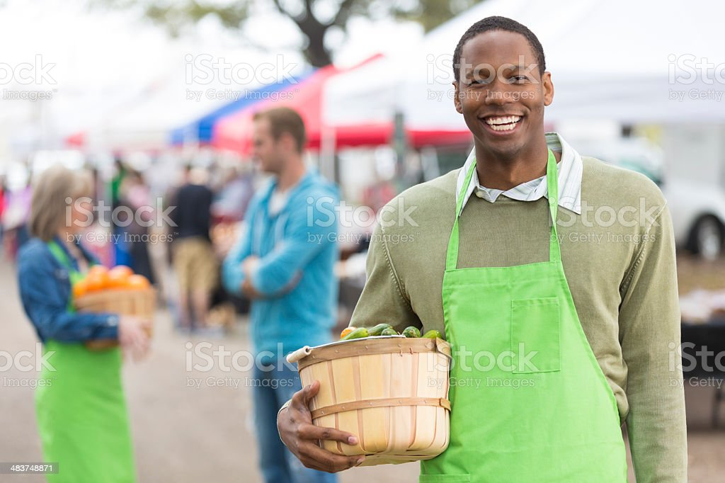 Friendly young man working at outdoor farmers market fair stock photo