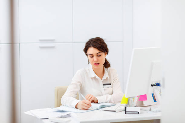 friendly young woman behind the reception desk administrator stock photo
