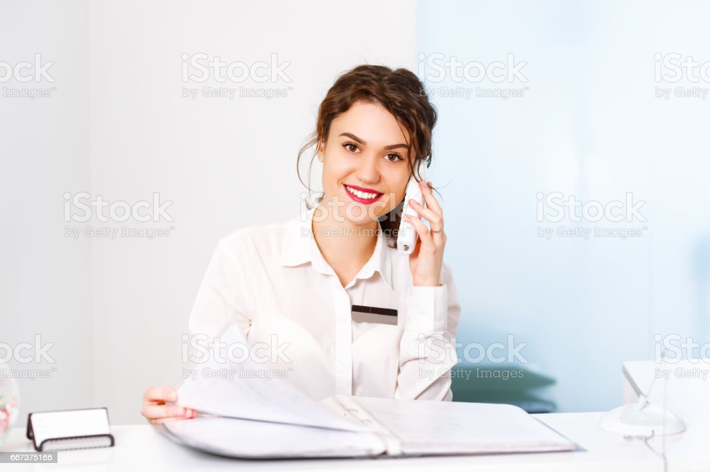 friendly young woman behind the reception desk administrator – Foto