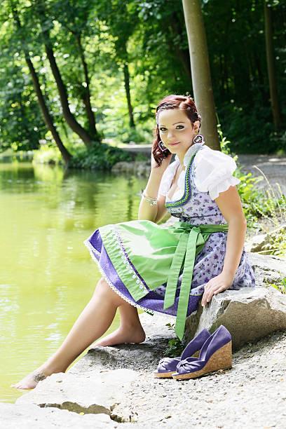 freundlichen jungen frau in violett dirndl kleid entspannenden sommer - moderne dirndl stock-fotos und bilder