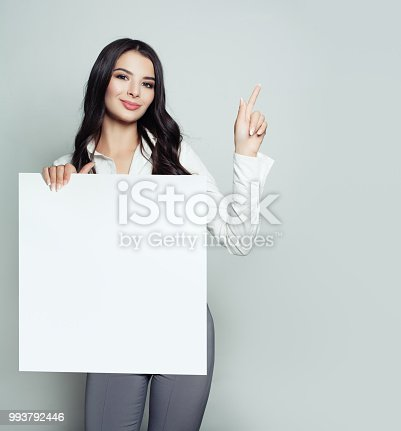 Friendly young woman with empty white blank paper banner background pointing her finger up. Girl smiling, business and education concept