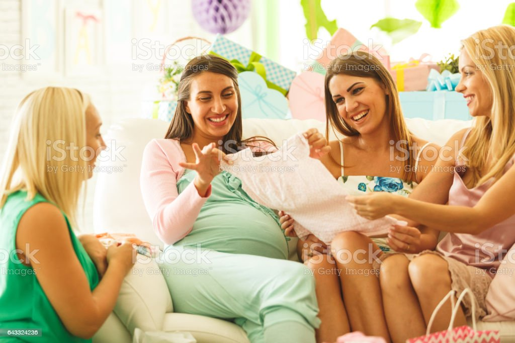 Friends Admiring Baby Clothing At Baby Shower Stock Photo More
