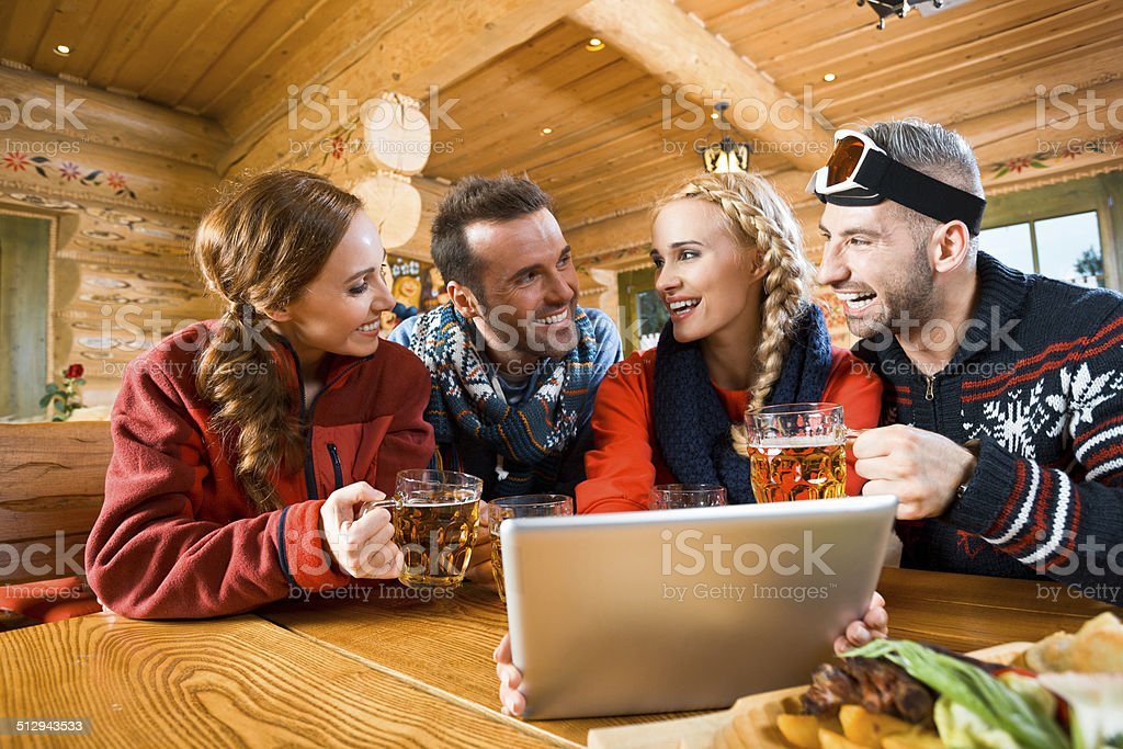 Friends after skiing Happy friends sitting in a mountain restaurant after skiing, enjoying beer and using a digital tablet together. Adult Stock Photo