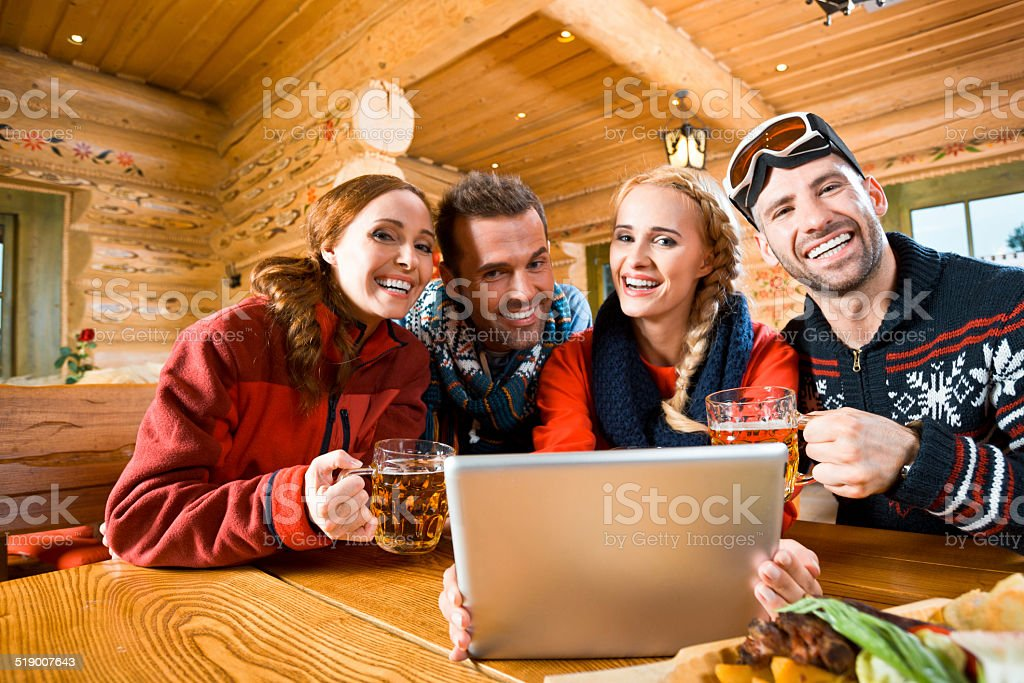 Friends after skiing Happy friends sitting in a mountain restaurant after skiing, enjoying beer and using a digital tablet together, smiling at the camera. Adult Stock Photo