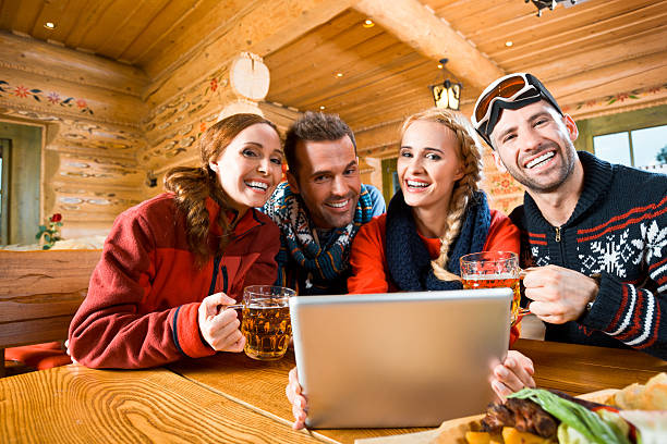 Friends after skiing Happy friends sitting in a mountain restaurant after skiing, enjoying beer and using a digital tablet together, smiling at the camera. russian dacha stock pictures, royalty-free photos & images