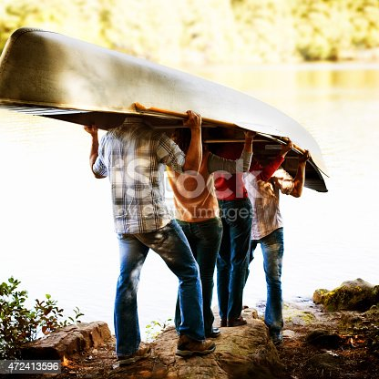 Group of friends carrying canoe to lake.