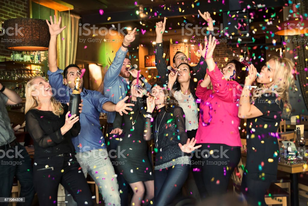 Friends and coworkers celebrating with confettis  in a bar. stock photo