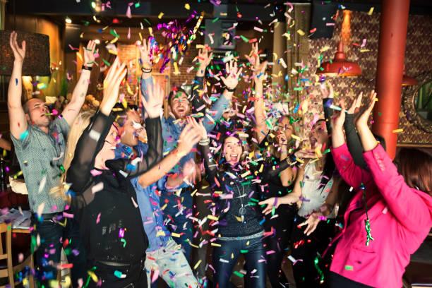 Freunde und Kollegen mit Confettis in einer Bar feiern. – Foto