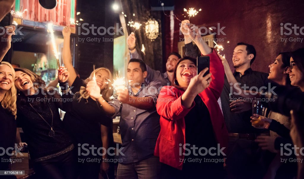 Friends and coworkers celebrating with sparklers in a bar. stock photo
