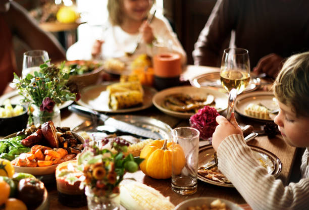 friends and families are gathering on thanksgiving day together - family dinner stock photos and pictures