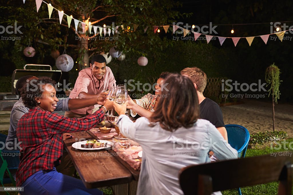 Friends and family making a toast at dinner party stock photo