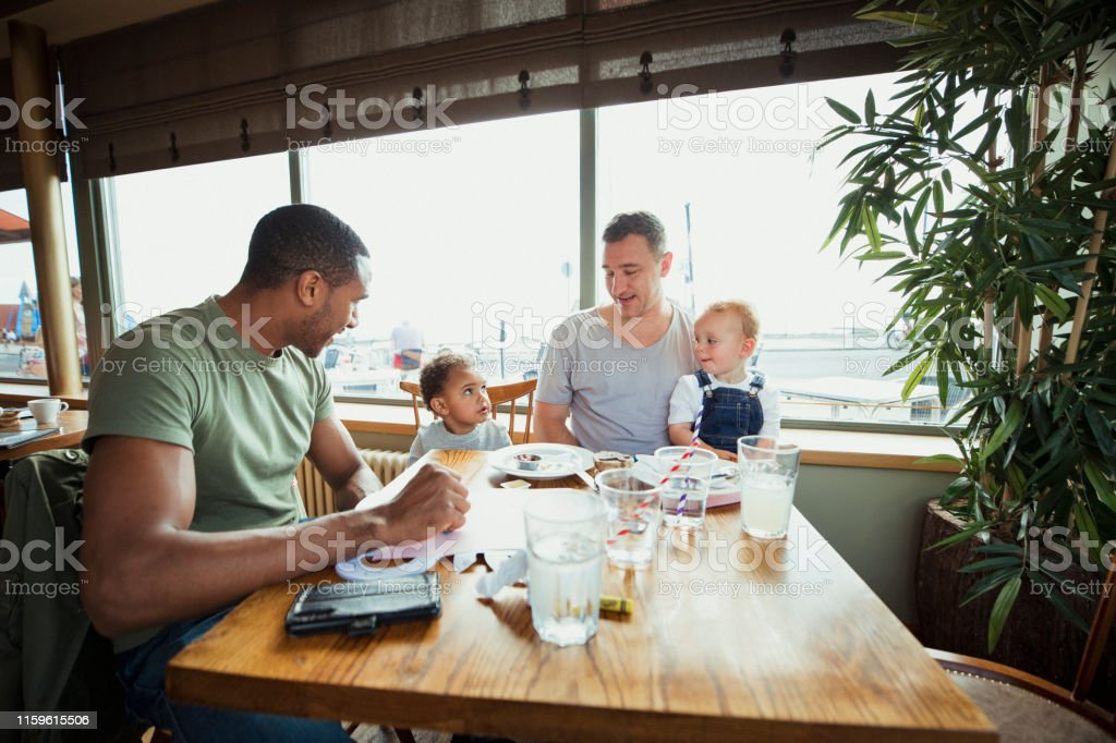 Friends and Sons Having Lunch Two men with their sons sitting at a table enjoying lunch together. 18-23 Months Stock Photo