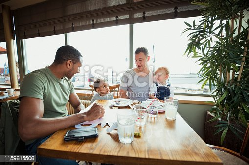 Two men with their sons sitting at a table enjoying lunch together.