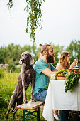 Friends And Their Dog Having Lunch Outdors