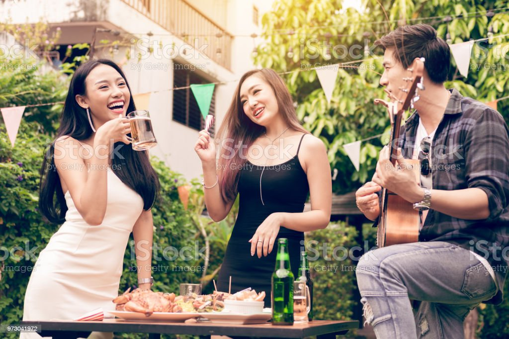 Friends are enjoying the celebration and have fun singing. stock photo