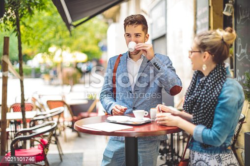 Friends are having a hot drink in a sidewalk cafe