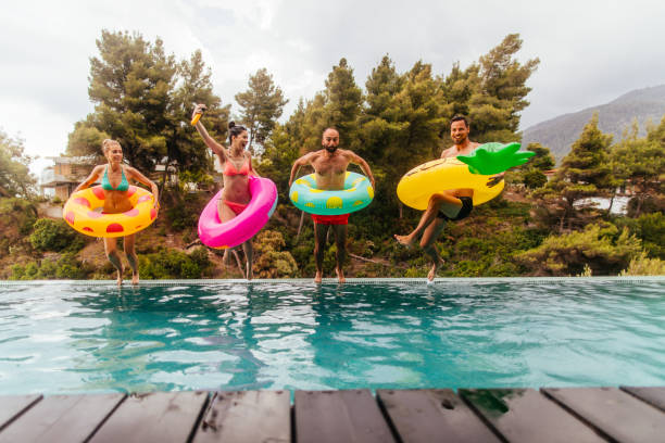 Friends are jumping into the pool Friends with inflatable rings jumping in the swimming pool swimming pool stock pictures, royalty-free photos & images