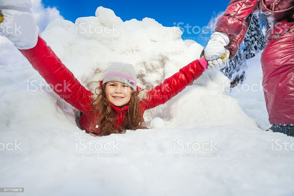 Friends are pulling smiling girl from snow tunnel stock photo