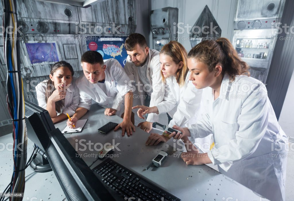 Friends are trying together to get out of escape room stock photo