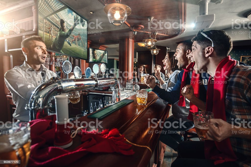 Friends are watching the soccer match and drinking beer on the bar stock photo