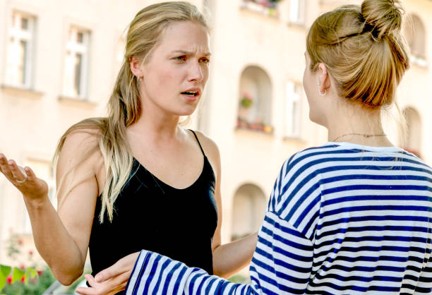 Friends arguing in street stock photo